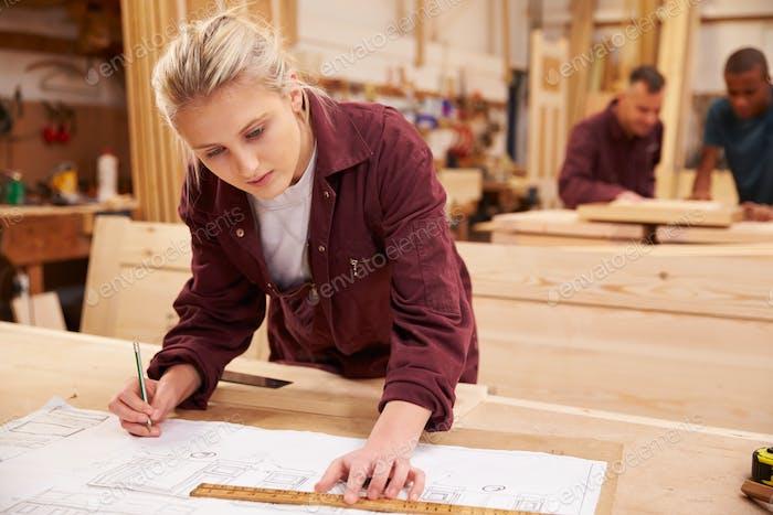 Zimmermann mit Lehrling Blick auf Pläne in Werkstatt