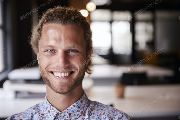 Millennial white male creative sitting in an office smiling to camera, head and shoulders close up