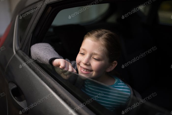 Teenage girl looking through car window