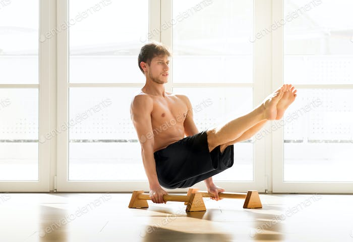 Man doing V sit pose when working out indoors