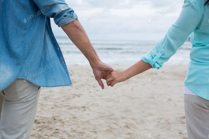 Mittlerer Abschnitt des Paares Hand am Strand