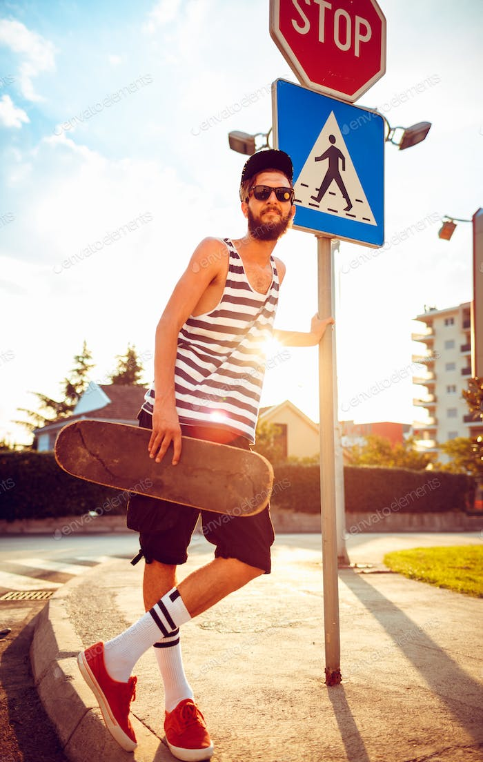 Stylish man in sunglasses with a skateboard on a street in the c