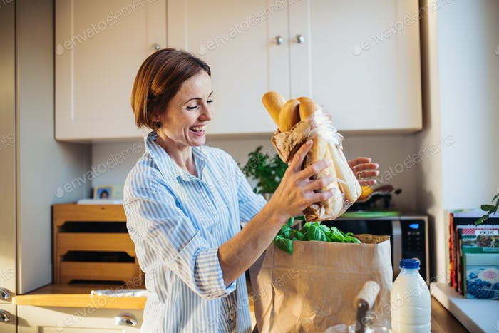 A young woman standing indoors in kitchen, unpacking shopping bag.