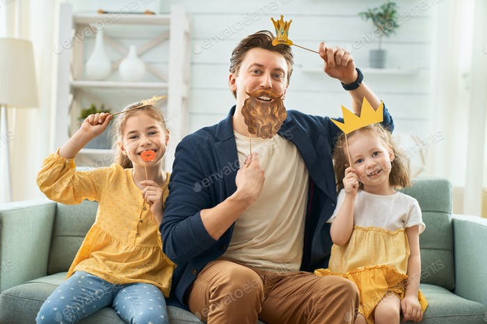 Father and his daughters with a paper accessories.