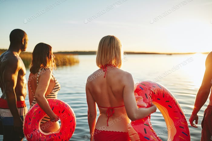 Friends in swimsuits watching the sunset together over a lake