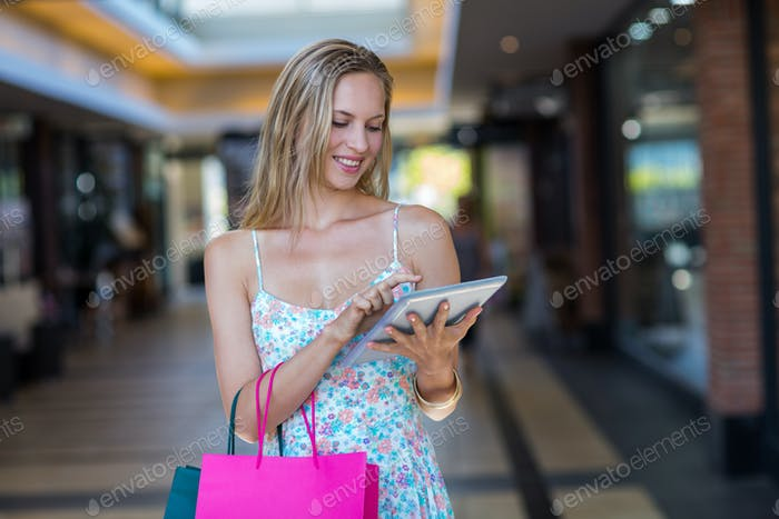 Smiling woman with shopping bags using tablet computer at shopping mall
