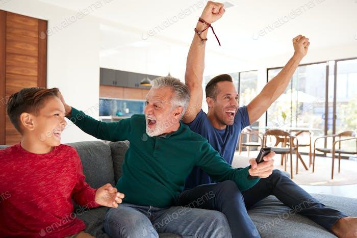 Excited Multi-Generation Male Hispanic Family Celebrating Watching Sports On TV