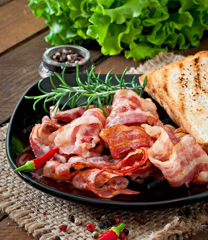 Fried bacon and toast on a black plate on a wooden background