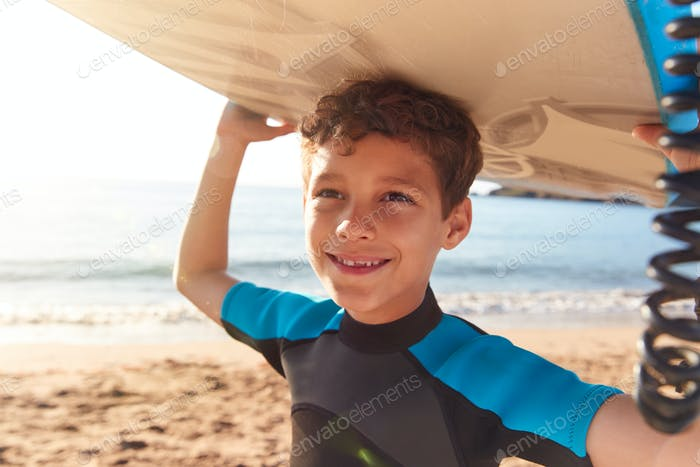Portrait Of Smiling Boy Wearing Wetsuit Carrying Bodyboards On  Summer Beach Vacation