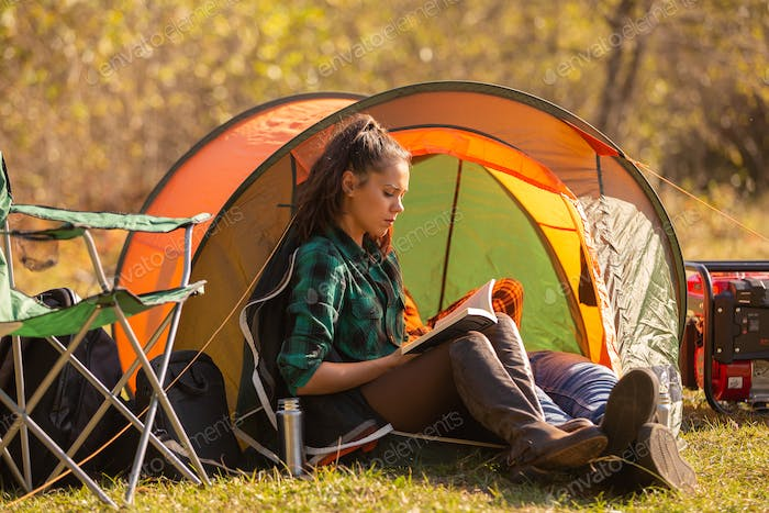 Young girl reading a book in front of the tent