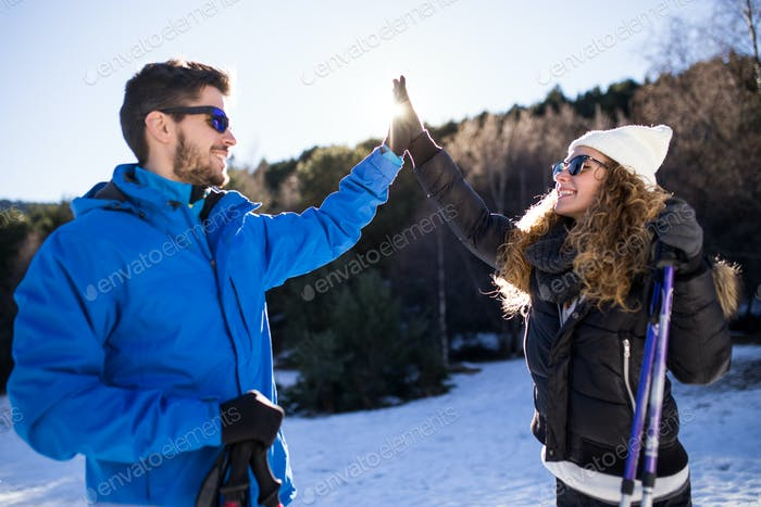 Happy young couple having fun over winter background.