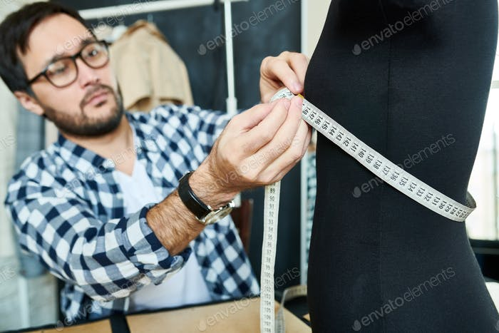 Man designing dress with mannequin