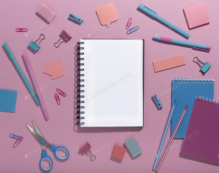 Notepad with blank space surrounded by creative office supplies