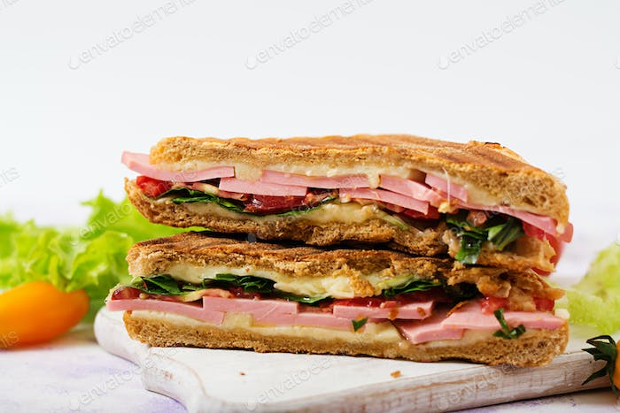 Club sandwich panini with ham, tomato, cheese and lettuce