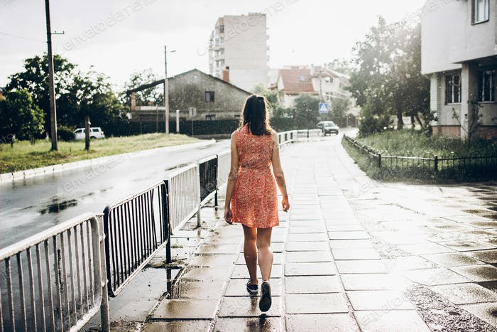 stylish hipster woman smiling and running in sunny rainy street in summer under rain