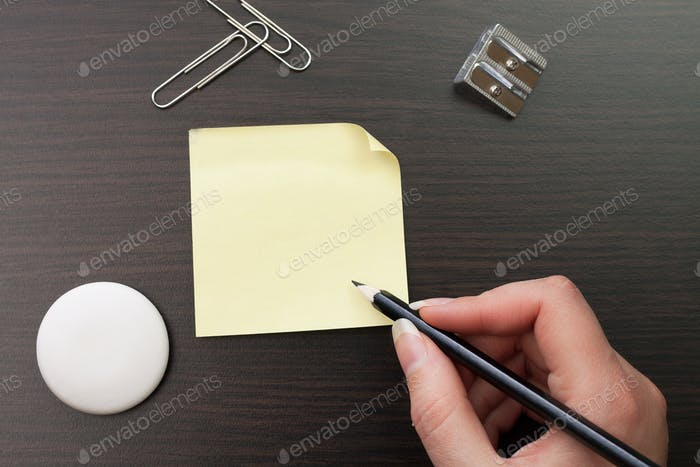 Woman Writing With Pencil On Yellow Sticker