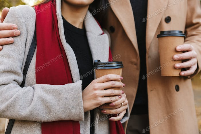 Cropped portrait of casual couple man and woman 20s drinking takeaway coffee