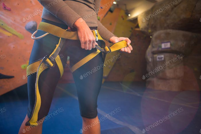 Mid section of woman wearing safety harness
