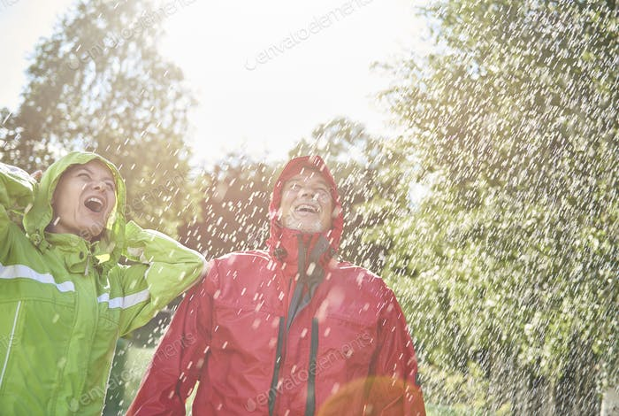 Exhilarated couple standing in rain