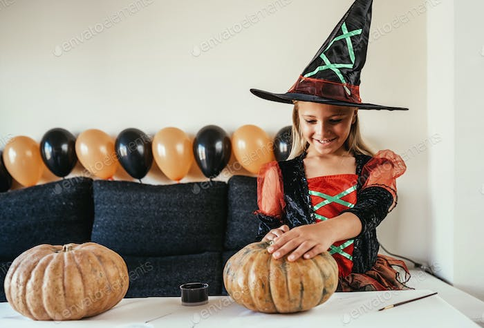 Beautiful girl disguised of witch decorating a pumpkin at home.