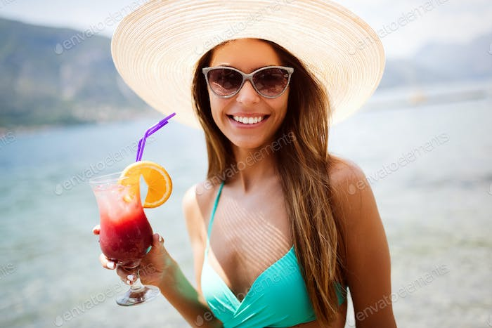 Happy beautiful woman drinking cocktail during summer vacation on beach