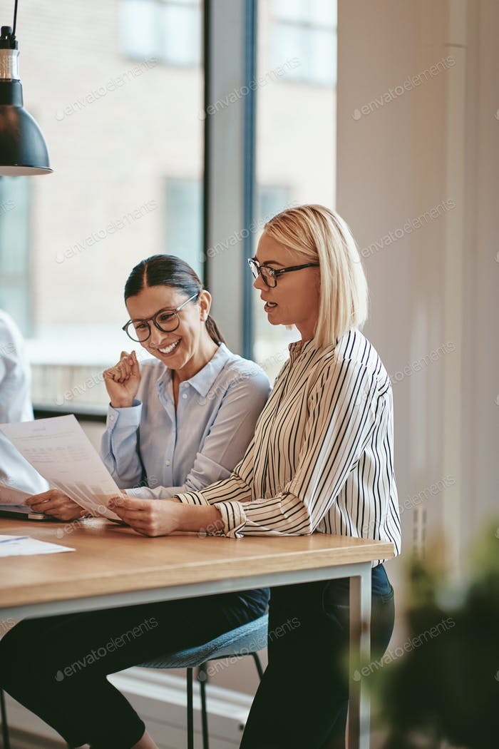 Smiling businesswomen reading paperwork together in an office boardroom