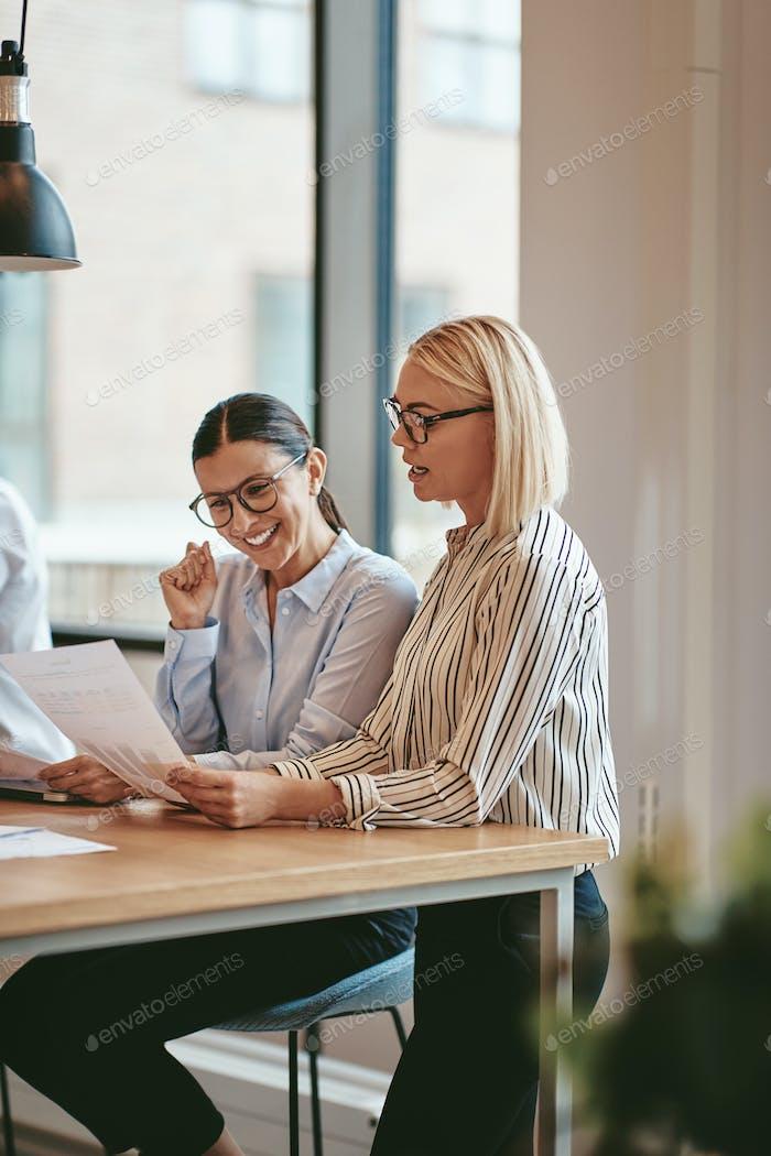 Улыбающиеся бизнесмены читать документы вместе в офисный зал заседаний