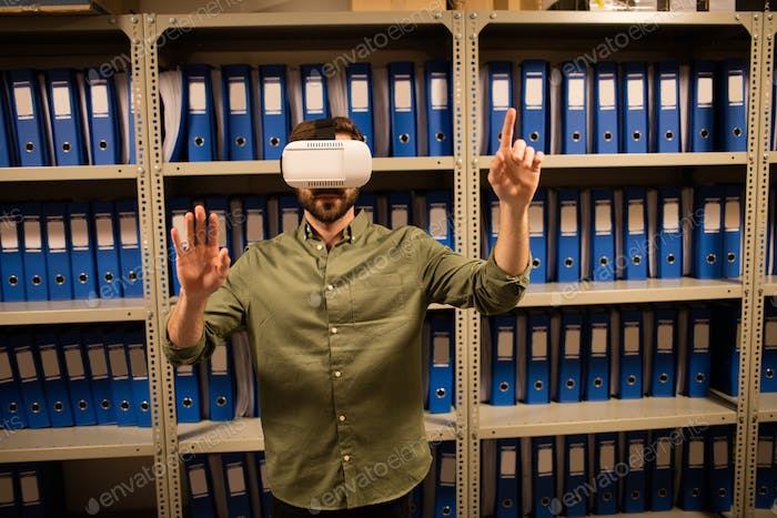 Businessman experiencing virtual reality in file storage room