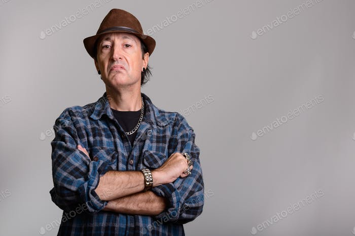 Studio shot of angry mature gangster man with arms crossed