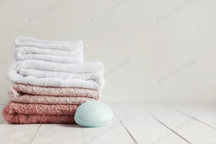 Wooden white table in the bathroom with a set of towels and scented soap