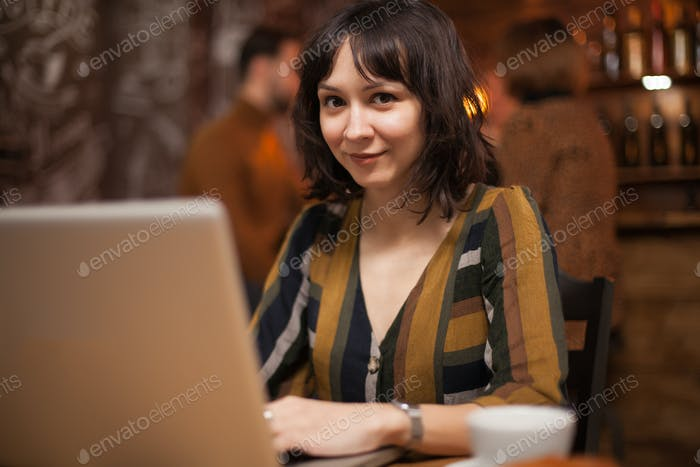 Pretty creative woman working on her laptop and looking to the camera in a coffee shop