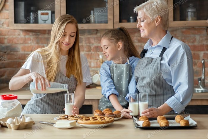 Caring mother pouring milk for family, having lunch together