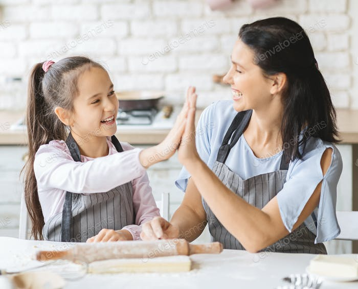 Cute girl and her mom giving high five in kitchen