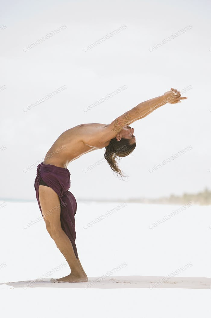 Young man stretching on the beach