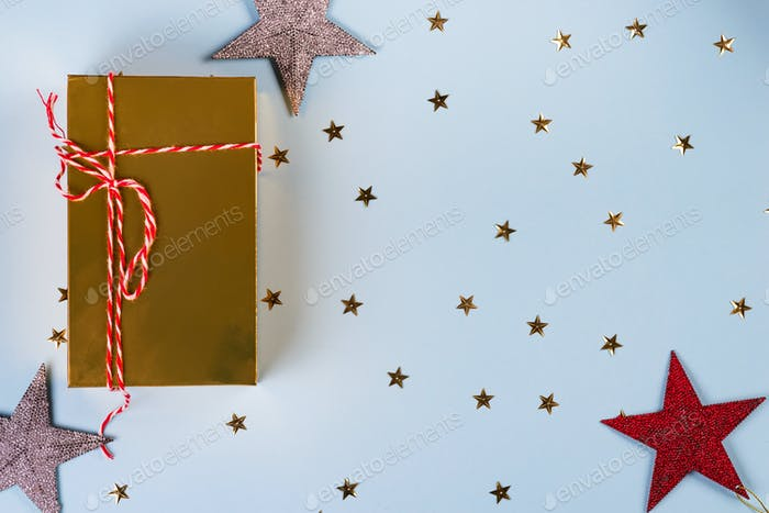 Christmas pattern made of golden, silver, red stars with golden gift box on blue background. Winter