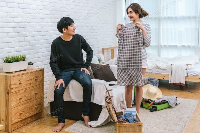 Glückliches asiatisches Paar wählt die Kleidung für die Vorbereitung auf die Reise im Wohnzimmer