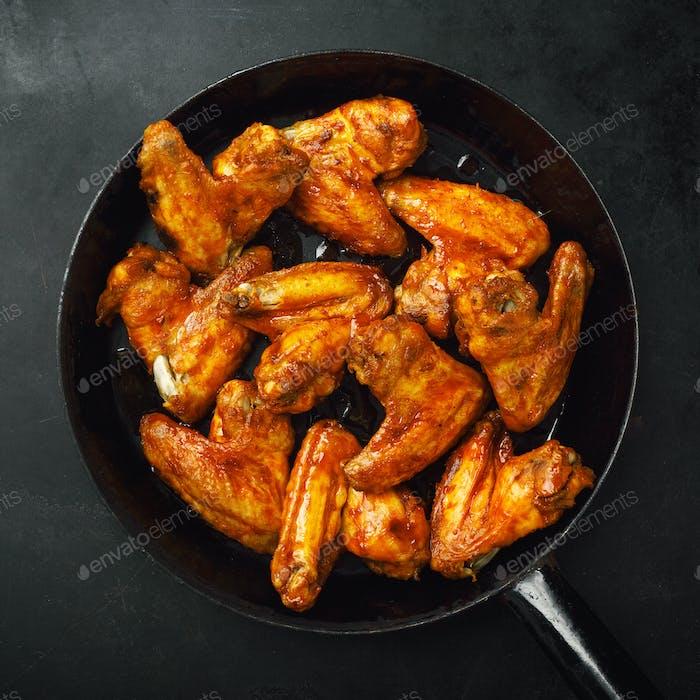Hähnchenflügel in Sauce auf Pfanne gegrillt