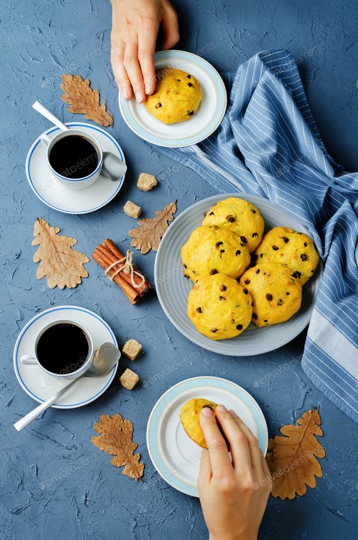 Chocolate chips pumpkin cookies with cups of coffee