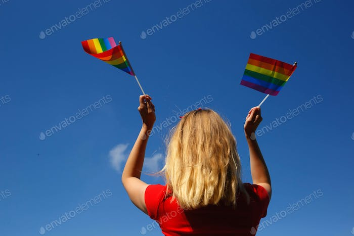 girl with lgbt flags behind her back against a bright blue sky