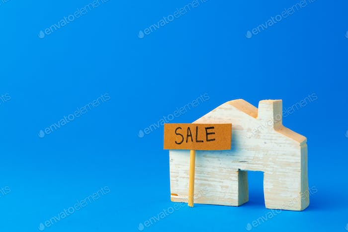 Wooden house model and for sale sign