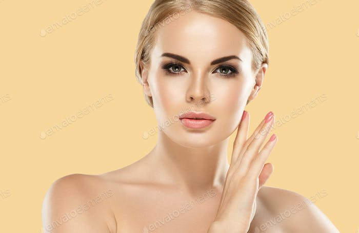 Beauty Woman with perfect healthy skin Portrait. Yellow background