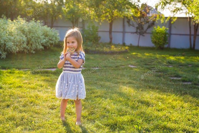 cute cauasian baby girl and big lollipop