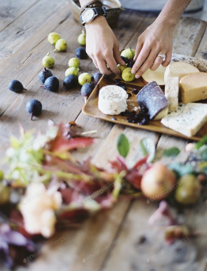 A woman at a kitchen table arranging fruit and cheese on boards.