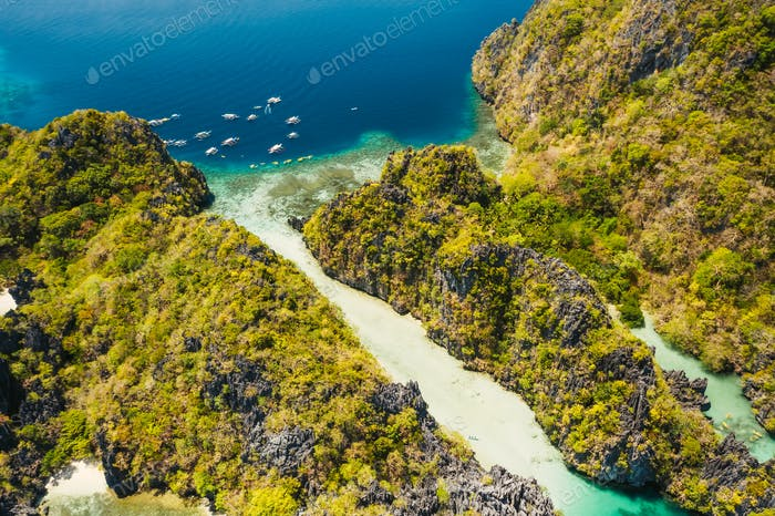 Palawan, Philippines aerial view of tropical Miniloc island. Tourism trip boats moored at entrance