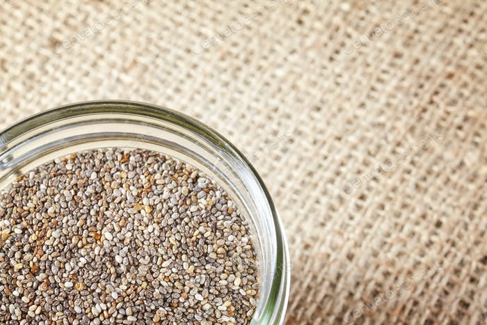 Close up of Chia seeds in a jar on linen background.