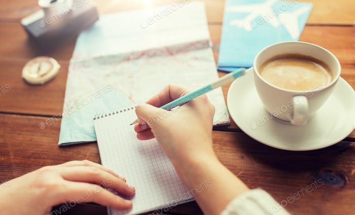 close up of traveler hands with notepad and pencil