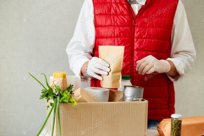 Helfen Sie  freiwillig in der schützenden medizinischen Maske und Handschuhe und legen Sie Lebensmittel in Spendenbox.