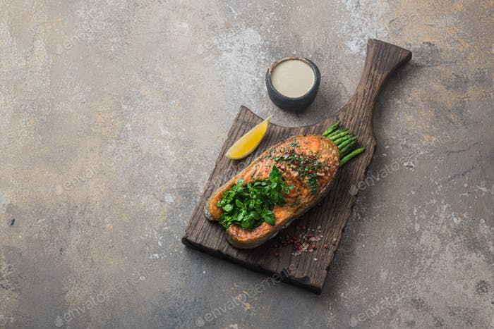 Fried salmon steak with asparagus on wooden board, copy space