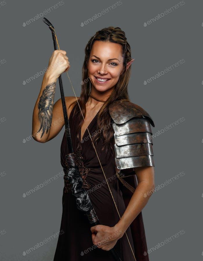 Lächelnde Kriegerin Frau hält Bogen.
