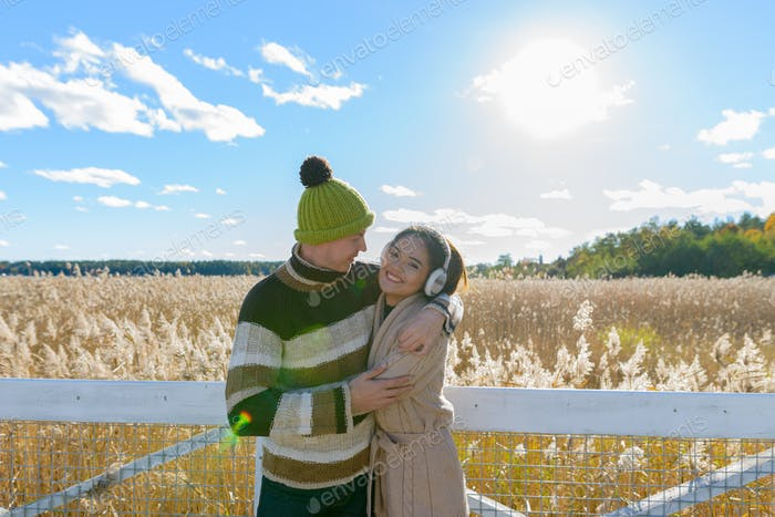 Happy young multi ethnic couple embracing each other against scenic view of autumn bulrush field